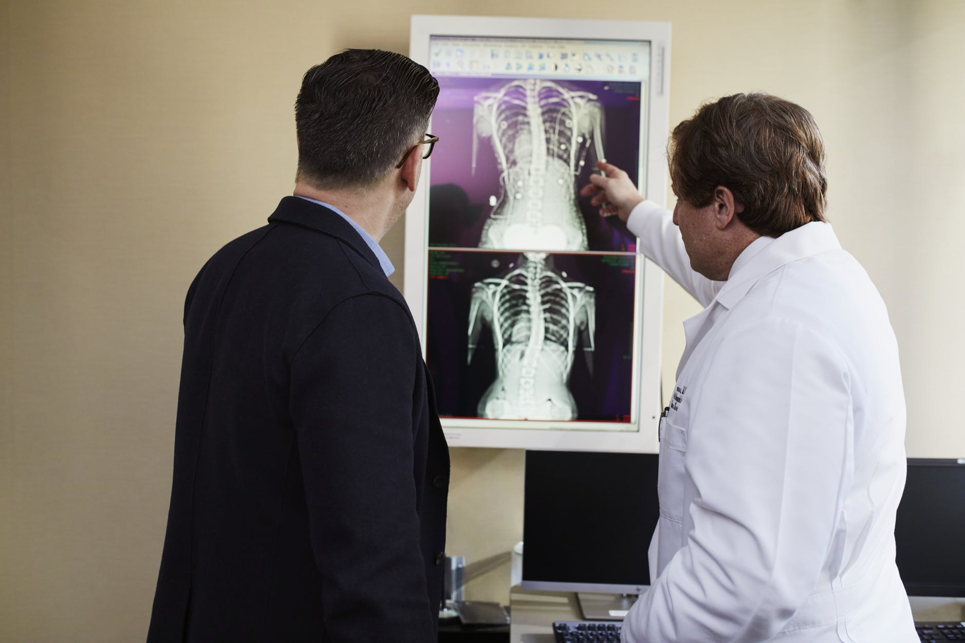 doctor pointing x ray result beside man wearing black suit