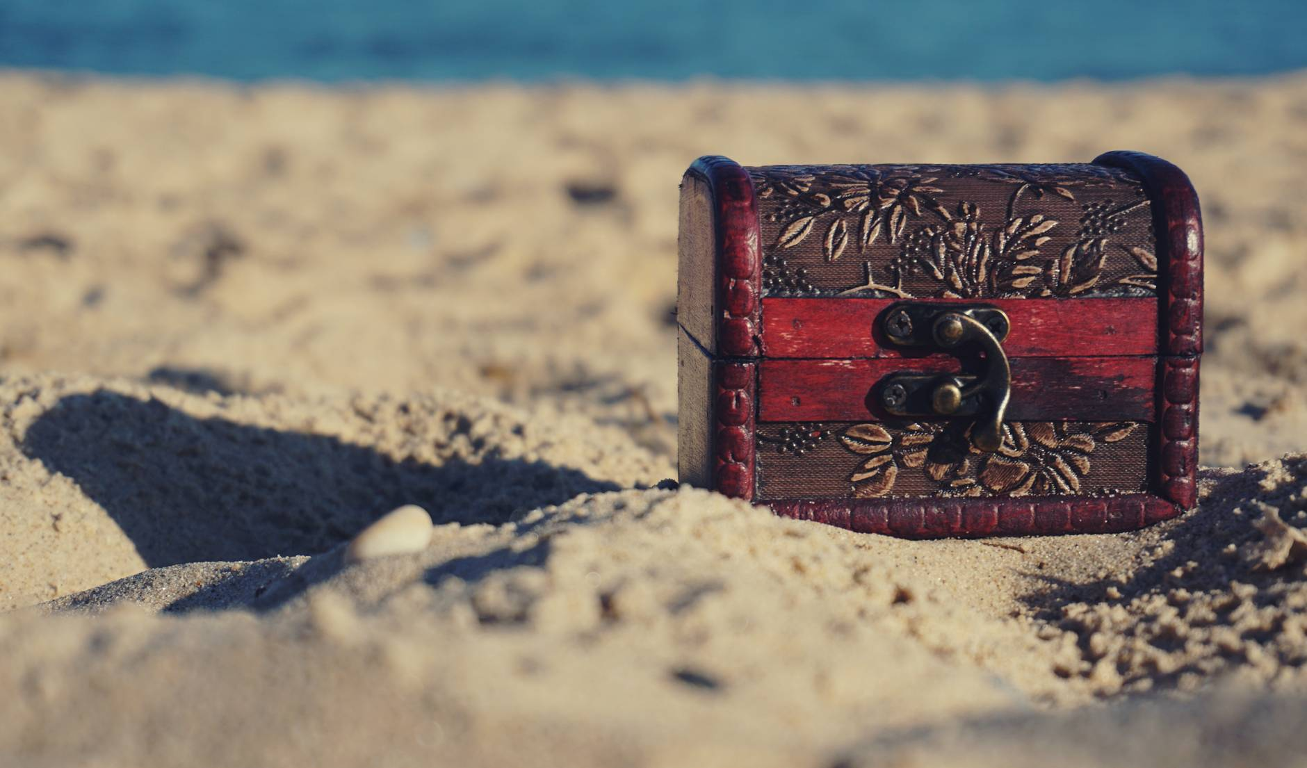 red and black wooden chest on white sand