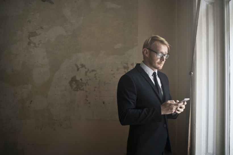 calm young businessman using smartphone in shabby room